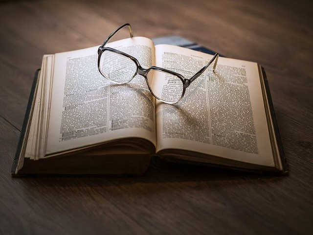 Open book with reading glasses on top